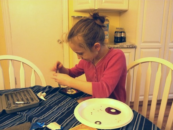 Baila taking an old hard drive apart to make a mobile.